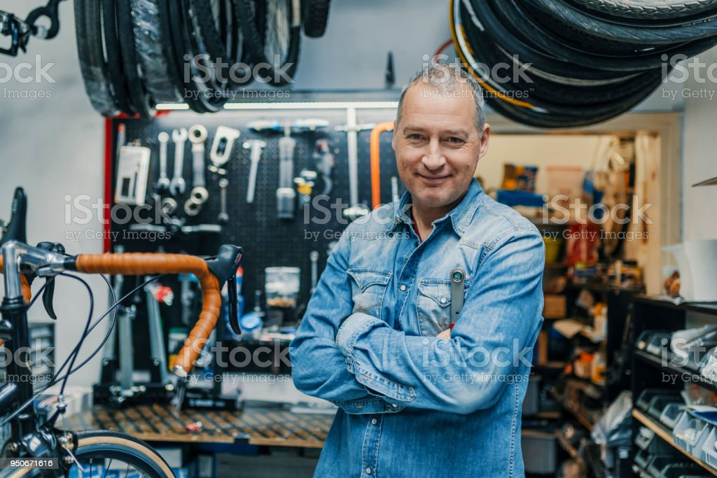 Stylish bicycle mechanic standing in his workshop royalty-free stock photo
