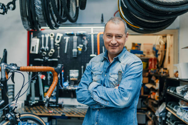stylish bicycle mechanic standing in his workshop - owner stock pictures, royalty-free photos & images