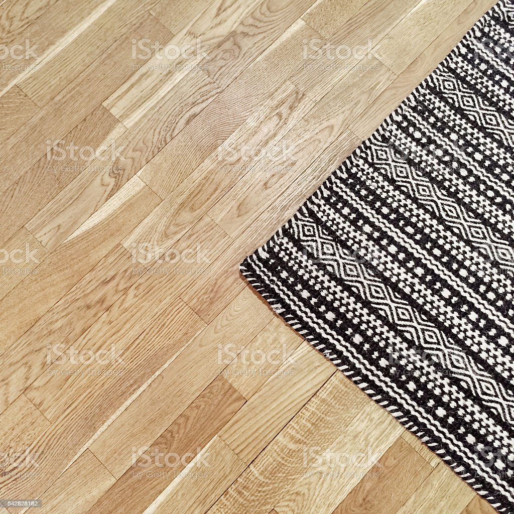 Stylish black and white rug on wooden floor stock photo
