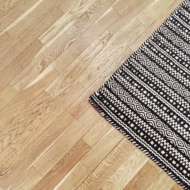 stylish black and white rug on wooden floor - teppich geometrisch stock-fotos und bilder