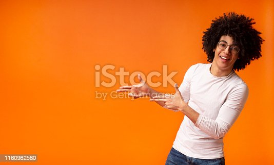 istock Stylish black man in glasses pointing away at empty space 1160982580