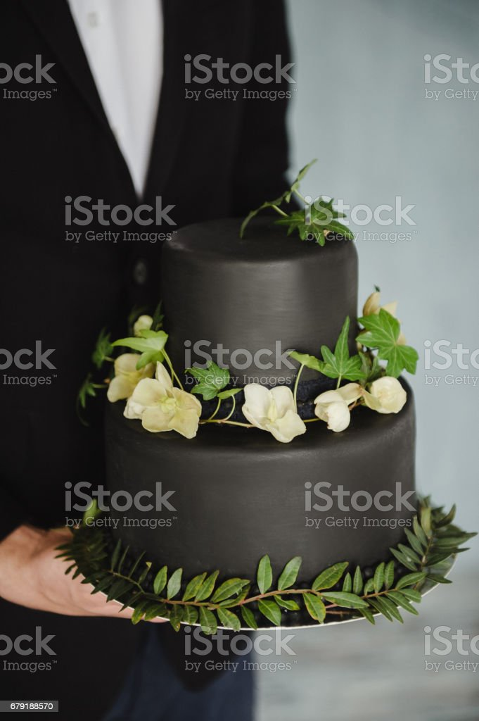 Stylish black wedding cake to the groom's hands stock photo