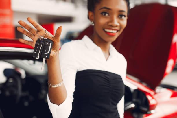 Stylish black woman in a car salon stock photo