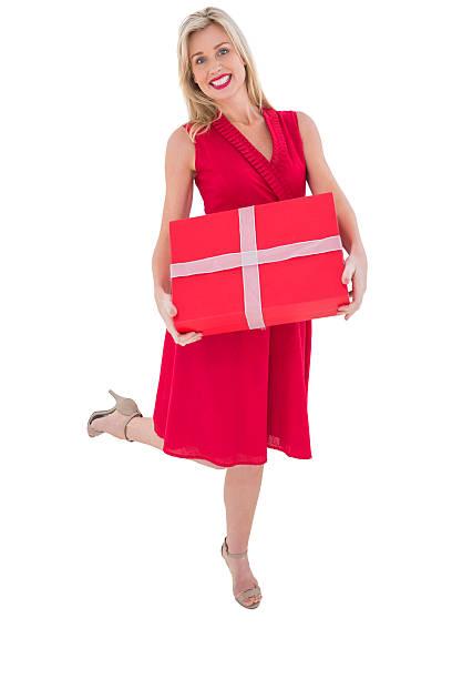 elegante blonde im roten kleid holding geschenk - wickelkleid lang stock-fotos und bilder