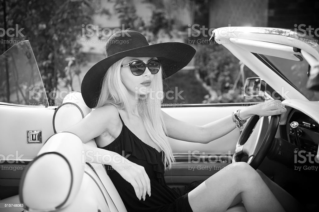 Stylish blonde vintage woman driving a convertible retro car stock photo