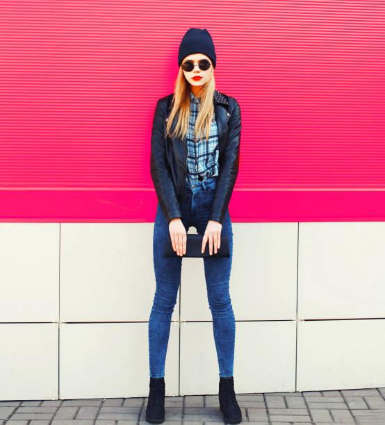 Stylisches blondes Damenmodel in voller Länge mit Rock schwarzen Jacke, Hut, mit Handtaschenkupplung auf der Stadtstraße über bunten rosa Wandhintergrund – Foto