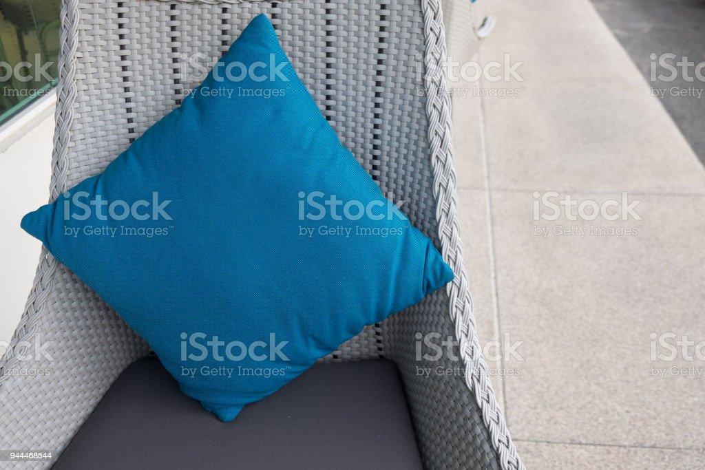 Stylish blue cushions decorating rattan sofa. Outdoor furniture.