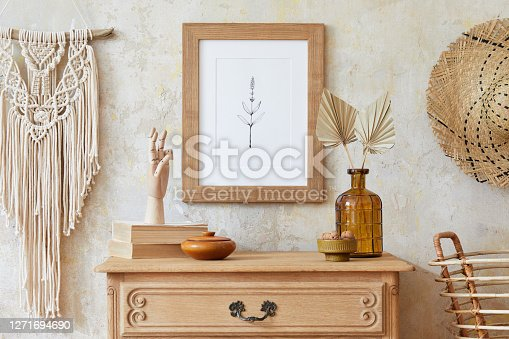 Beige boho interior of living room with mock up poster frame, elegant accessories in stylish home decor. Template. Wabi sabi concept.