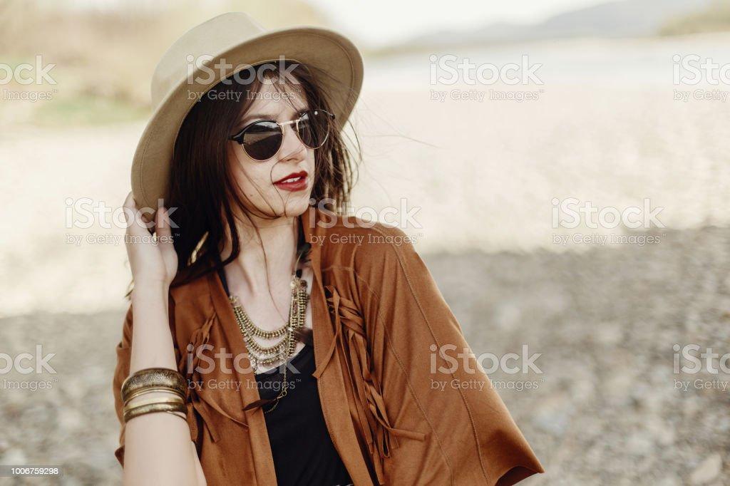 ad7674b6e Foto de Boho Elegante Mulher De Óculos Segurando O Chapéu Com Cabelo ...
