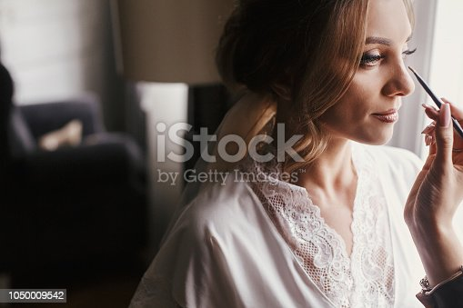 istock Stylish bride getting her make-up in the morning at window light. Makeup artist doing brows and applying eyeshadow on bride face close-up. 1050009542