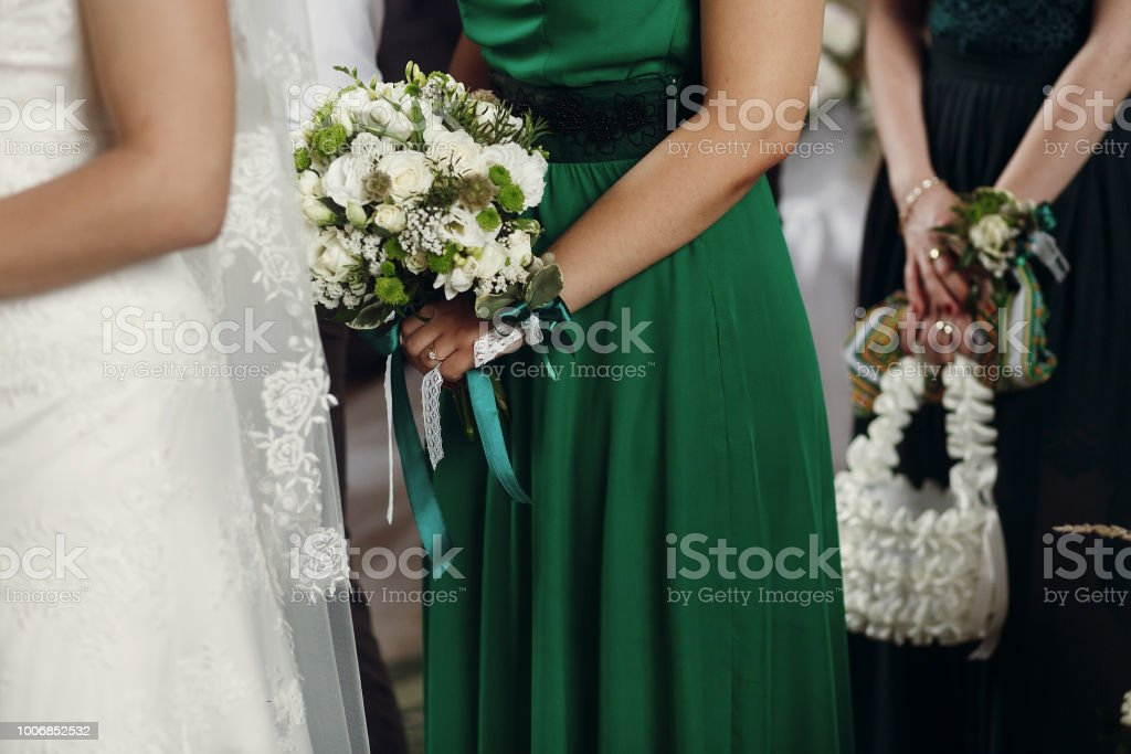 stylish bridesmaid standing holding wedding bouquet in old church at marriage ceremony stock photo