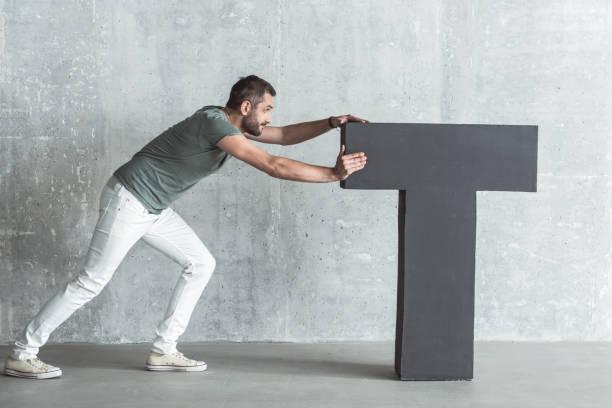 Stylish bristled guy is shoving large symbol stock photo