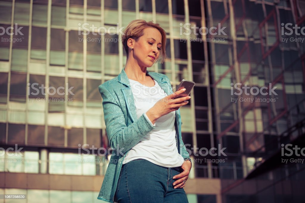 Stylish business woman texting in front of the office building stock photo