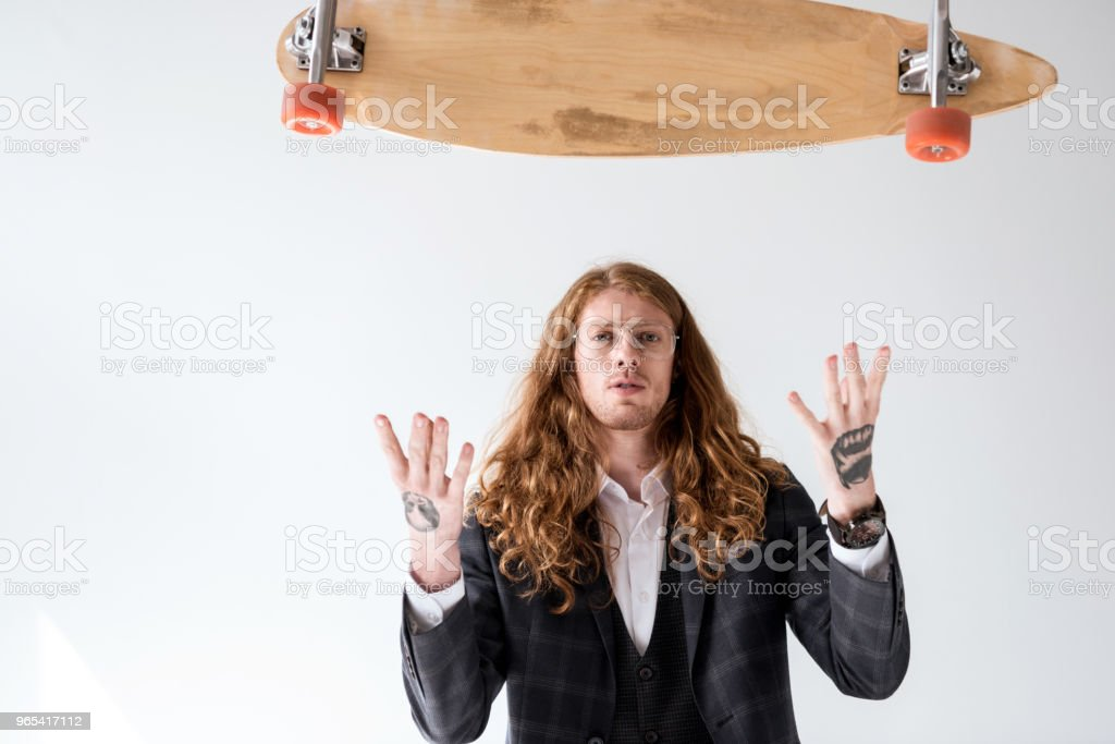 stylish businessman with curly hair catching falling longboard isolated on white royalty-free stock photo