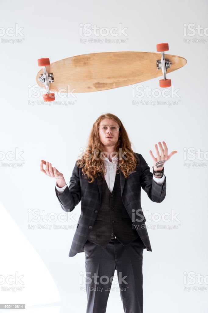 stylish businessman with curly hair catching falling skateboard zbiór zdjęć royalty-free