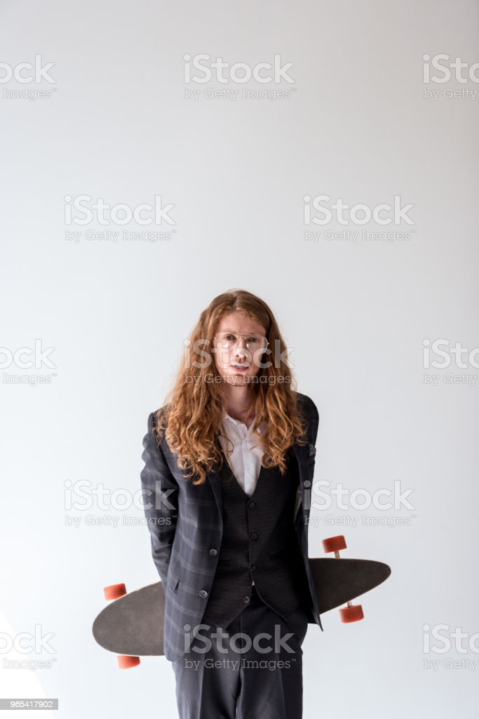 stylish businessman with curly hair holding longboard isolated on white royalty-free stock photo