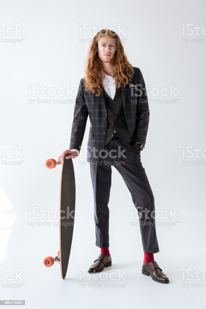stylish businessman with curly hair posing with longboard royalty-free stock photo