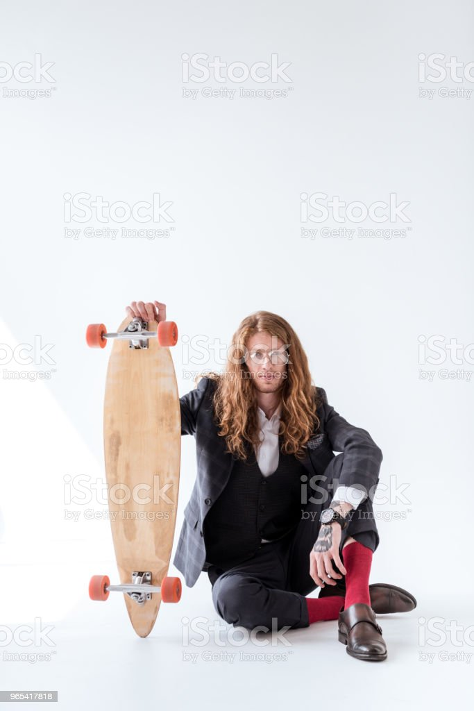 stylish businessman with curly hair sitting on floor and holding skateboard royalty-free stock photo