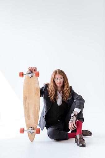 곱슬 머리 바닥에 앉아와 스케이트 보드를 들고 세련 된 사업 경영자에 대한 스톡 사진 및 기타 이미지