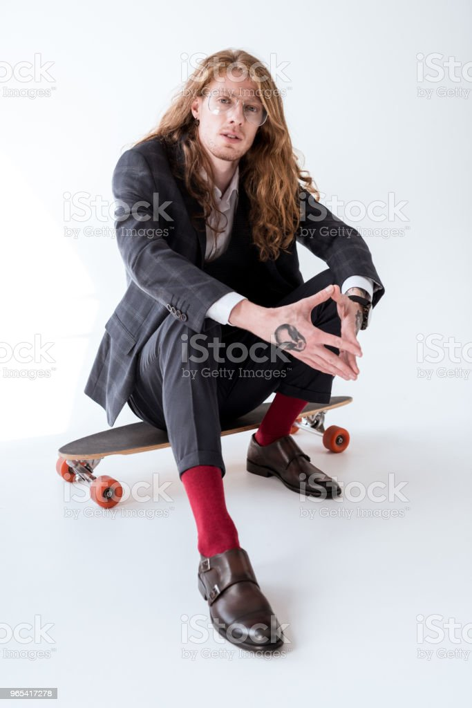 stylish businessman with curly hair sitting on skateboard zbiór zdjęć royalty-free