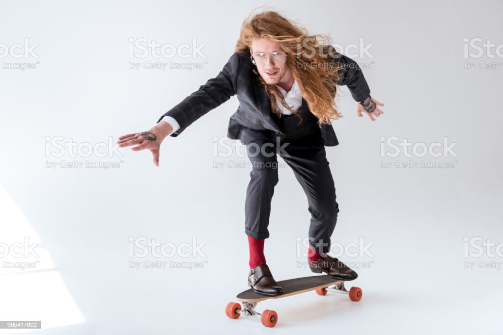stylish businessman with curly hair skating on longboard royalty-free stock photo