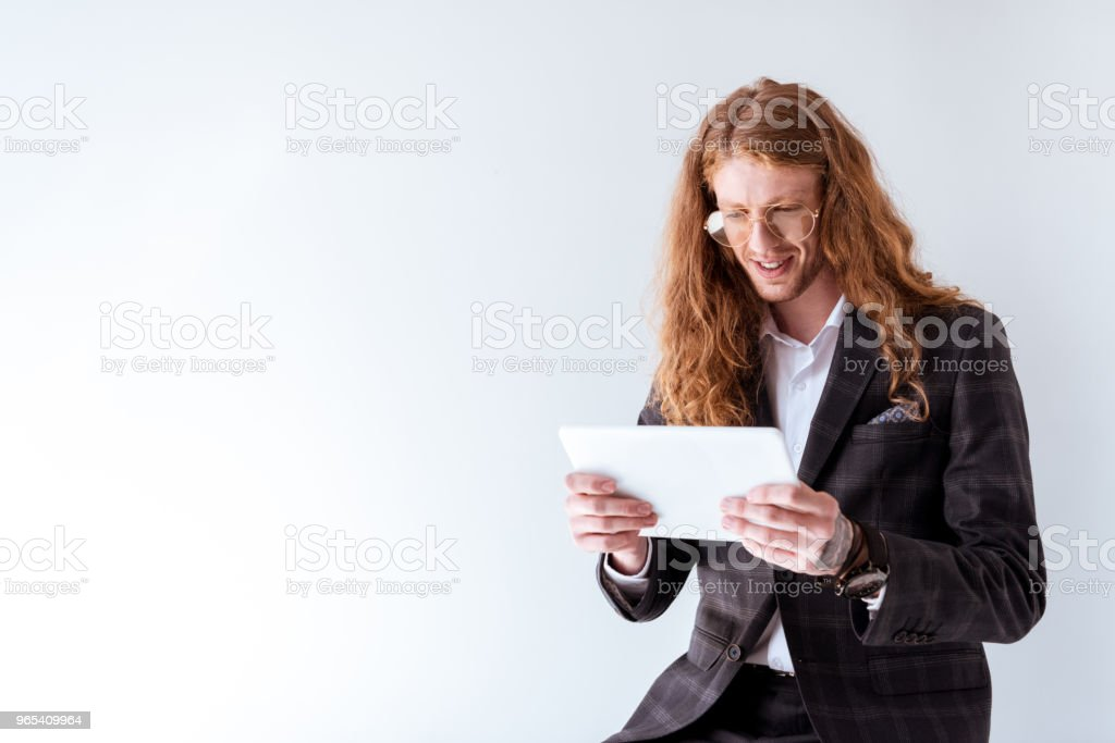 stylish businessman with curly hair using tablet isolated on white zbiór zdjęć royalty-free