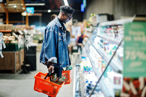 Stylish casual african american man at jeans jacket and black beret at supermarket. stock photo