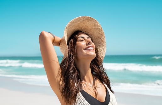 Beautiful girl with straw hat enjoying sunbath at beach. Close up face of young tanned woman with closed eyes enjoying breeze at seaside. Carefree latin woman smiling with ocean in background.