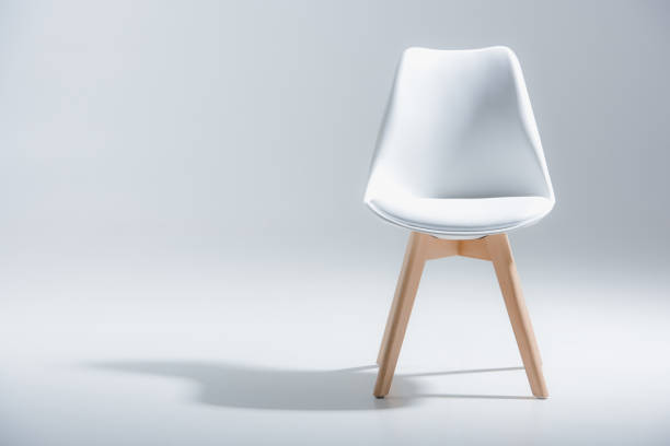 stylish chair with white top and light wooden legs standing on white stock photo