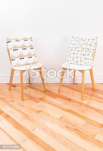 994217090 istock photo Stylish chairs with ornamental cushions on hardwood floor 972247946