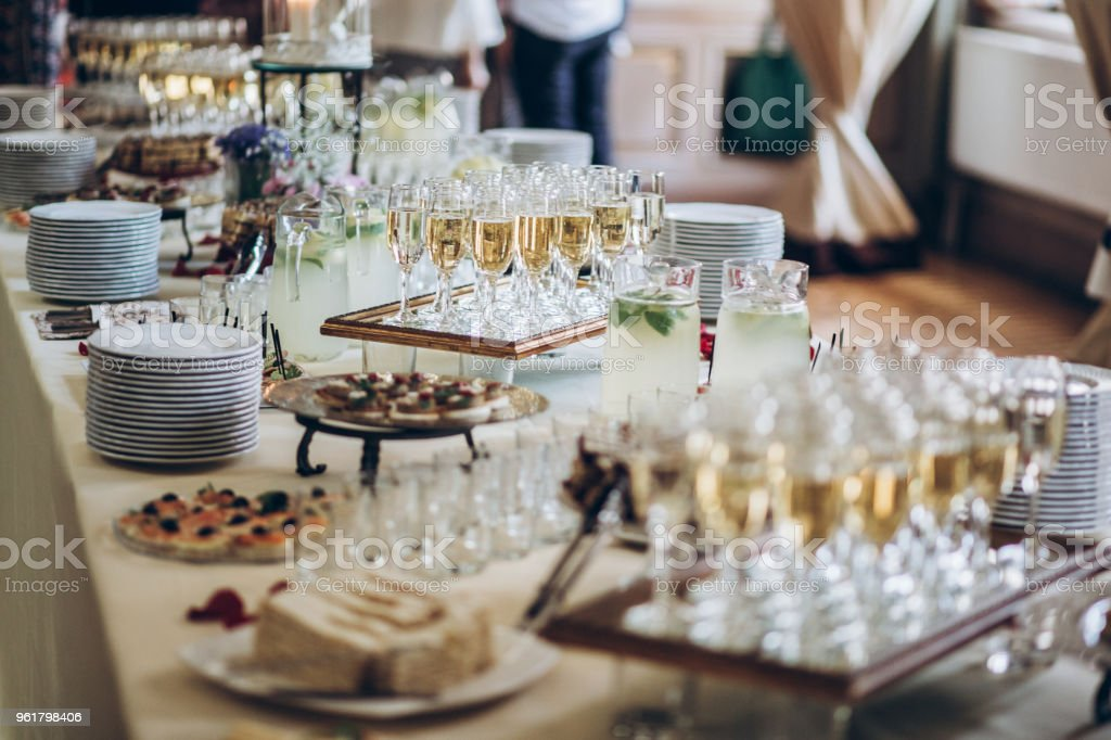 stylish champagne glasses and food  appetizers on table at wedding reception. luxury catering at celebrations. serving food and drinks at events concept stock photo