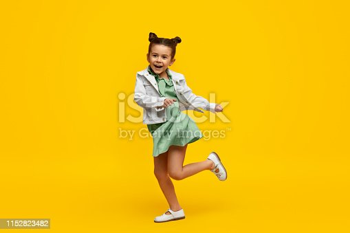 istock Stylish child smiling and dancing 1152823482