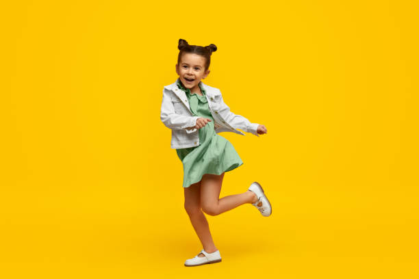 Stylish child smiling and dancing Adorable little girl in trendy dress and jacket cheerfully smiling and twisting on one leg while dancing against bright yellow background dancing stock pictures, royalty-free photos & images