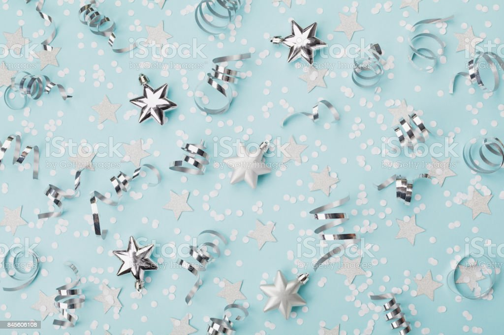 Stylish christmas background with confetti, serpentine and silver stars top view. stock photo