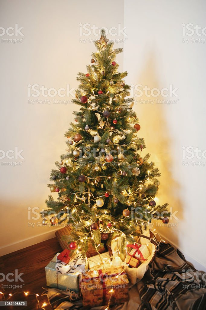 Stylish Christmas Gift Boxes Under Beautiful Christmas Tree With Ornaments Golden Lights And Presents In Festive Room Red And Gold Balls On Pine Tree Branches Decor For Winter Holidays Stock Photo