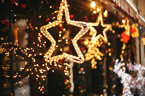 Stylish christmas golden star illumination and fir branches with red and gold baubles, golden lights bokeh on front of building at holiday market in city street. Christmas street decor