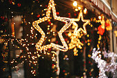 istock Stylish christmas golden star illumination and fir branches with red and gold baubles, golden lights bokeh on front of building at holiday market in city street. Christmas street decor 1175684792