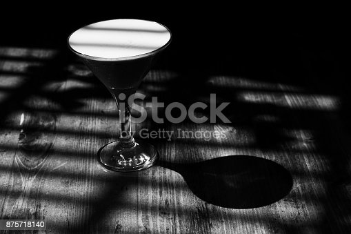 istock Stylish classic cocktail Clover Club in the shadows and rays of light. Black white monochrome effect photo 875718140