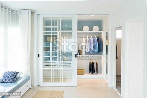 istock Stylish clothes and accessories in large wardrobe closet 1132795962