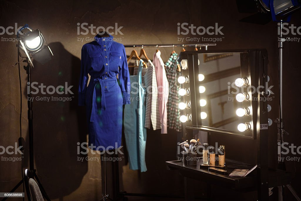 Stylish clothes and make-up products in dressing room stock photo