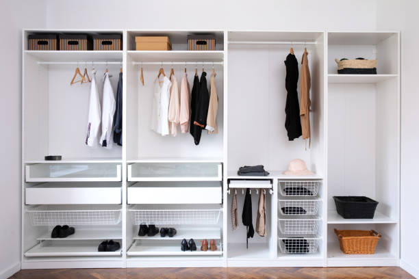 Stylish clothes, shoes and home stuff in large wardrobe closet. – zdjęcie