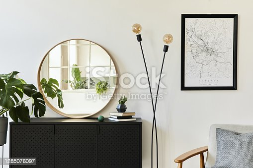 istock Stylish composition of living room interior with design black commode, a lot of plants, round mirror, decoration and elegant personal accessories. template. Modern home decor. 1285076097