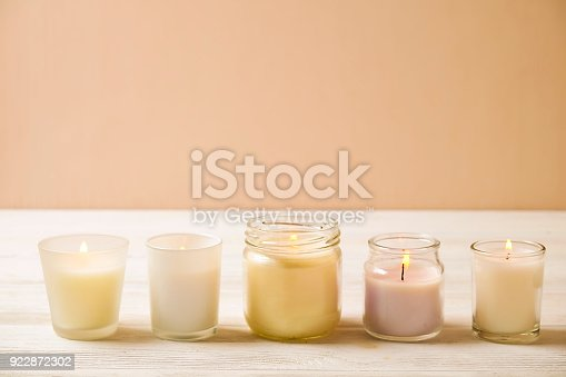 Minimal spa treatment composition. Various burning aroma candles on white wood textured table background. Feminine relaxing atmosphere. Close up, copy space, top view.