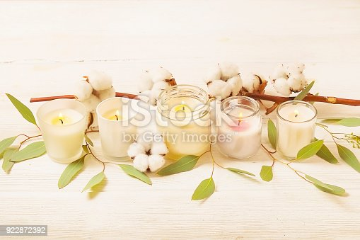 Minimal spa treatment composition. White burning aroma candle, cotton boll & eucalyptus leaves on white wood textured table background. Feminine relaxing atmosphere. Close up, copy space, top view.