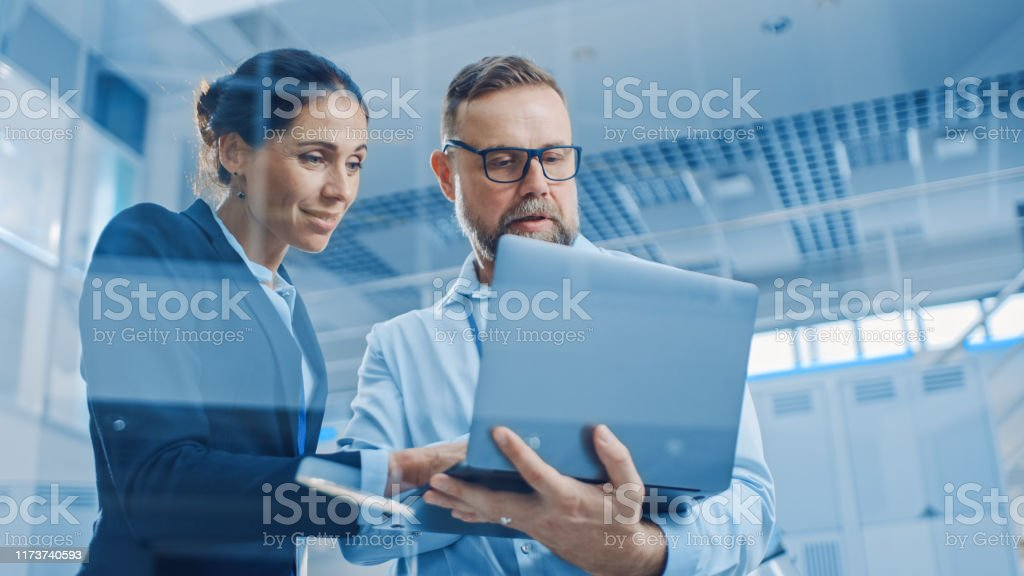 Stylish Confident Businesswoman and Businessman Working on a Project, Man Holds Laptop Computer, They Reference it. In the Background Modern and Bright Facility. Low Angle Shot Stylish Confident Businesswoman and Businessman Working on a Project, Man Holds Laptop Computer, They Reference it. In the Background Modern and Bright Facility. Low Angle Shot Adult Stock Photo