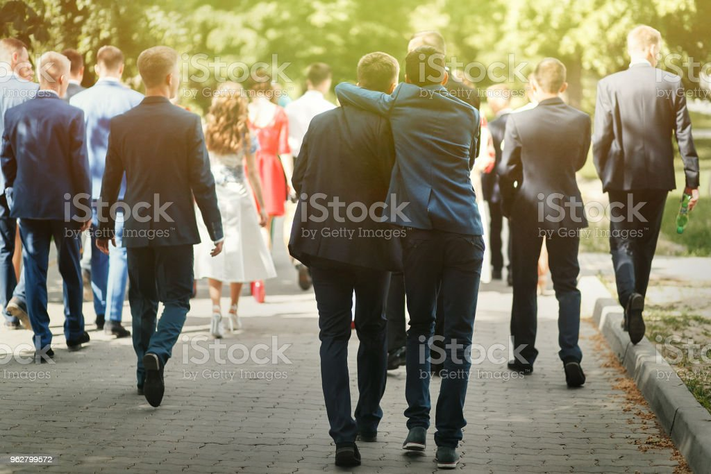 stylish confident man in suit having fun, group of people walking, reception at luxury wedding, rich graduation at school or university stock photo