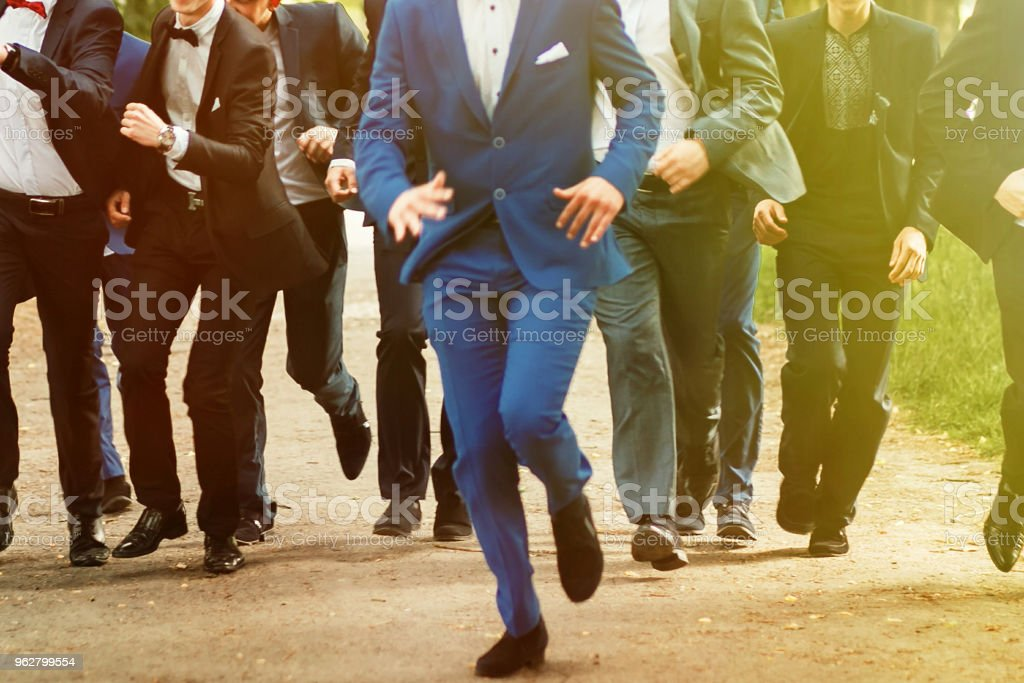 stylish confident men in suit running, reception at luxury wedding, rich graduation at school or university, business meeting stock photo