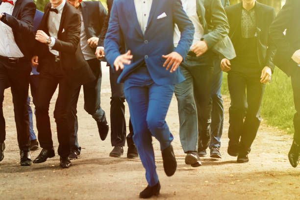 stylish confident men in suit running, reception at luxury wedding, rich graduation at school or university, business meeting - prom fashion stock photos and pictures