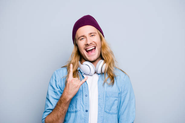 Stylish cool joyful guy with long blonde hair is dressed in denim jeans clothes, is listening to music and showing horn-gesture, he is a student of high school, isolated on grey background stock photo