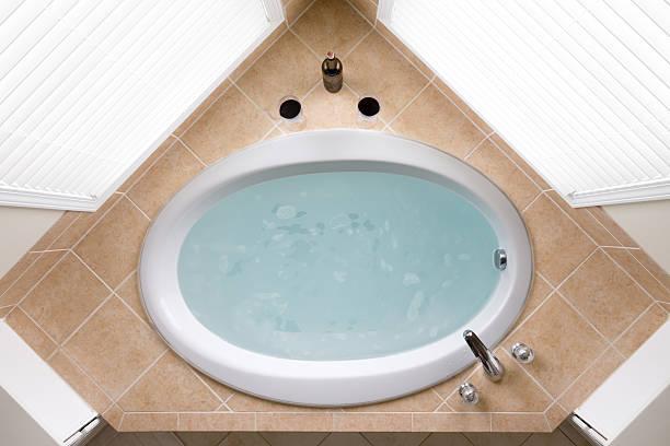 Stylish corner oval bathtub in a tile surround stock photo